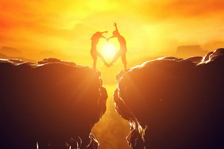Happy couple making heart shape over precipice between two rocky mountains at sunset. Love unique concept.